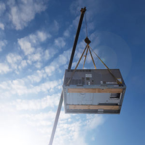 A new HVAC unit being lifted by a crane