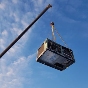 An old HVAC unit being lifted by a crane